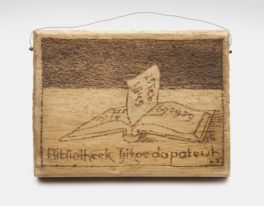 """Small wooden board with a book and the text """"Bibliotheek Tjikoedapateuh"""" (Library Tjikoedapateuh).<br/>NIOD Collectie 417-089b"""