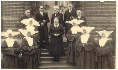 Het vieren van jubileum Gon Driesen, huishoudster van de pastoors : foto aan achterzijde Cantine met zusters dochterds van Liefde van Nuth. v.l.n.r.: 1. zuster Appolien; 2. zuster Josephine; 3. keuken zuster Henrica; 4. Assistent rector T. Houben van het College van Weert; 5. Niek Schallenberg, commies aan het kanaal; 6. Gon Driesen (huishoudster v); 7.Sjang Verheijden, bakker in de kantine; 8. Ernst Hoijer, employe op de zinkfabriek; 9. meester Jansen, schoolhoofd; 10.  zuster Veronica van de bewaarschool; 11. moeder overste zuster Julienne; 12. zuster Celesta van de naaischool;