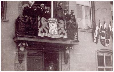 Het toespreken van de Budelse bevolking door een militair vanaf het balkon van het raadhuis. 1. van Hunsel; 2. van Hout; 3. van Geloven; 4. onbekend; 5. onbekend; 6. engelse militair; 7. A. Glaudemans; 8. A. Ras; 9. zoon Piet