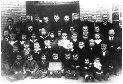 Leerlingen en leraren Openbare Lagere school : zittend rechts, Mr. Winkelmolen, links hoofd vd school Frans van Hoorn, staand rechts J. Verrek (Henselmans) en Em Kneepkens zittend links: 18. hoofd vd school Frans van Hoorn; zittend rechts: 34. Mr. Winkelmolen; staand: 35. Em Kneepkens; staand rechts: 45.J. Verrek (Henselmans);